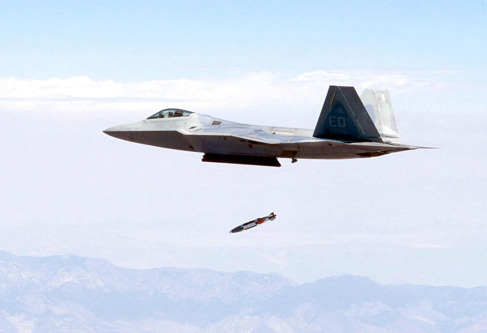 An F 22 Raptor, flown by Maj. John Teichert, releases a guided bomb unit-32 1,000-pound joint direct attack munitions at supersonic speed for the first time near California's Panamint Mountain range.