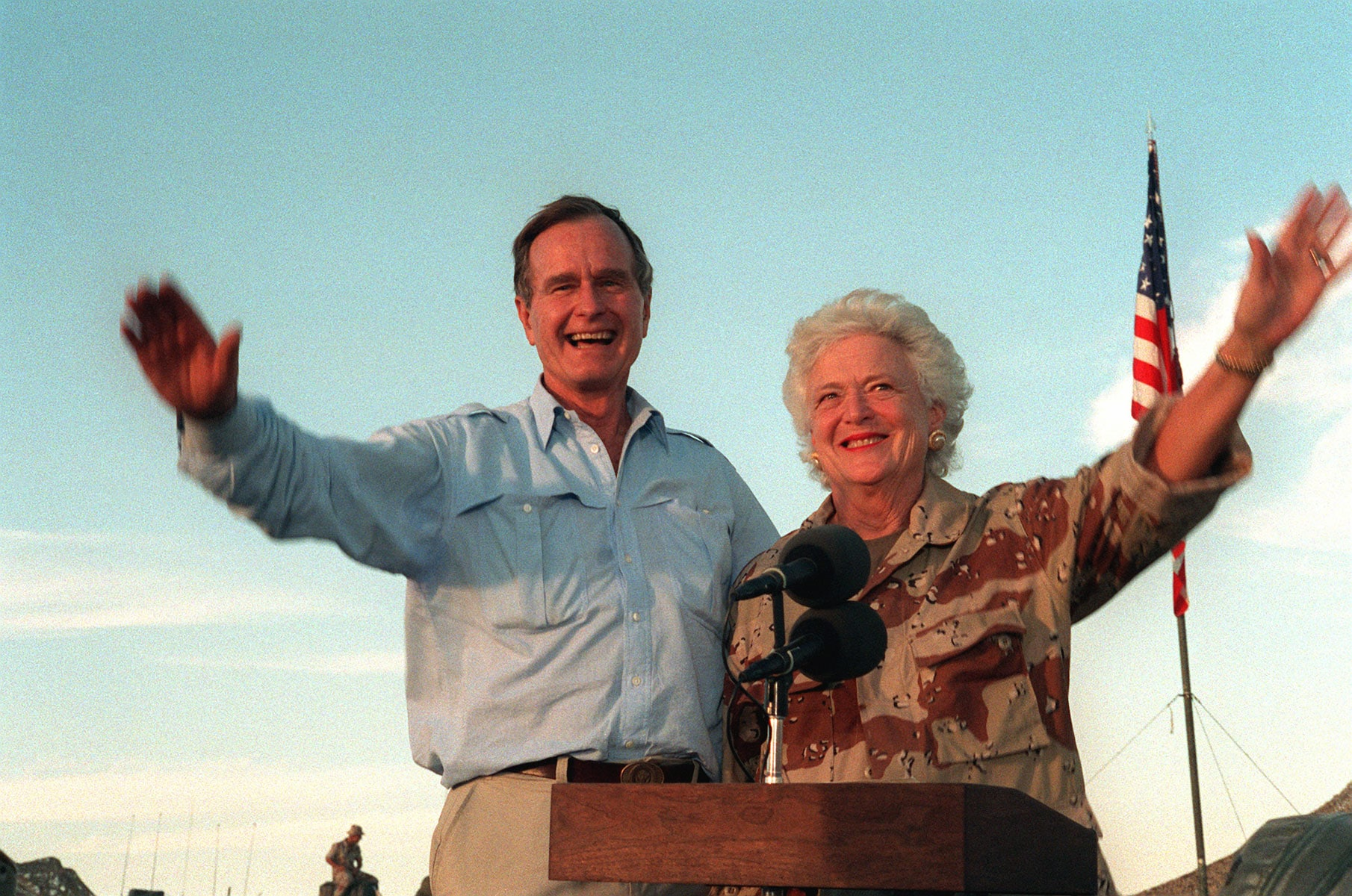 U.S. President George H.W. Bush and first lady Barbara Bush wave as they stand in the back of a vehicle during a visit to a desert encampment in Saudi Arabia, Nov. 22, 1990.