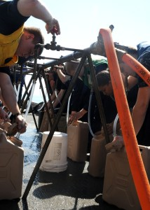 Sailors aboard the USS Carl Vinson (CVN 70) fill water jugs to be distributed to Haitians affected by the recent earthquake. Official USN photo.