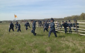 Midshipmen struggle to maintain alignment while scaling a fence during Pickett's Charge