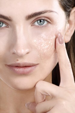 Beautiful woman applying scrub treatment on face closeup