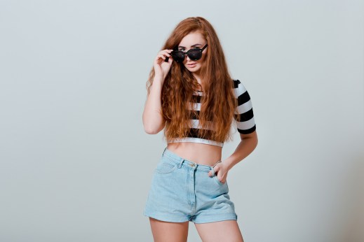 Portrait of beautiful sexy young girl in jeans shorts and sun glasses on white background