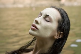 Spa Outdoor Beautiful young woman lying with natural dead sea facial mask on her face