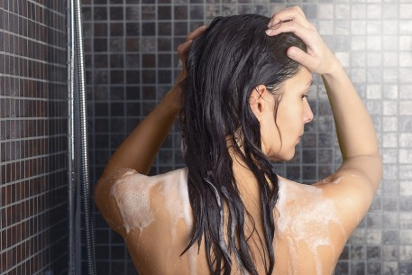 Young woman washing her long hair under the shower standing with her back to the camera rinsing it off under the jet of water with her head partially turned to the side over grey mosaic tiles