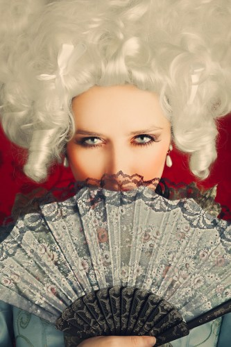 Baroque style portrait of a young beautiful woman behind a hand fan