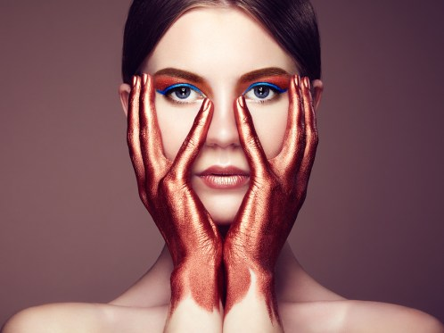 Portrait of beautiful young woman with art make-up. Bronze hand. Beauty fashion