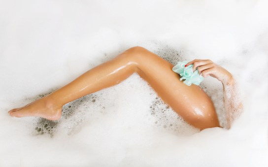 Woman in bath washing leg in bathtub with a lot of bubble bath foam. Leg of beautiful young woman in bath in bathroom.