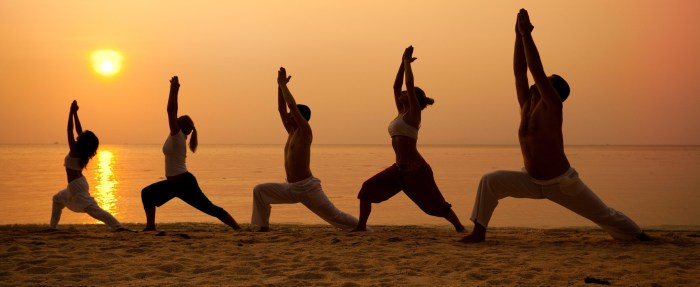 yoga on the beach with sun in background