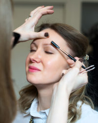 Make-up artist combing eyebrow on model's face.