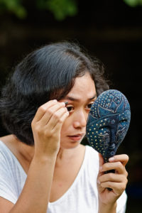 asian ethnic young adult female picking eyebrow