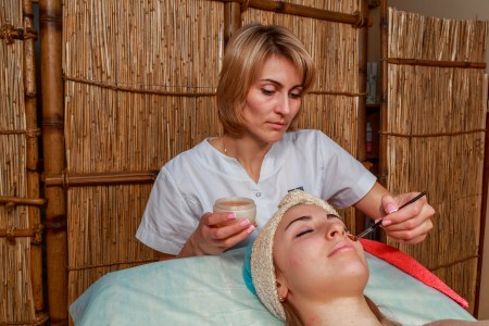 Beauty treatments for problem skin. The girl in the spa salon applying cream.