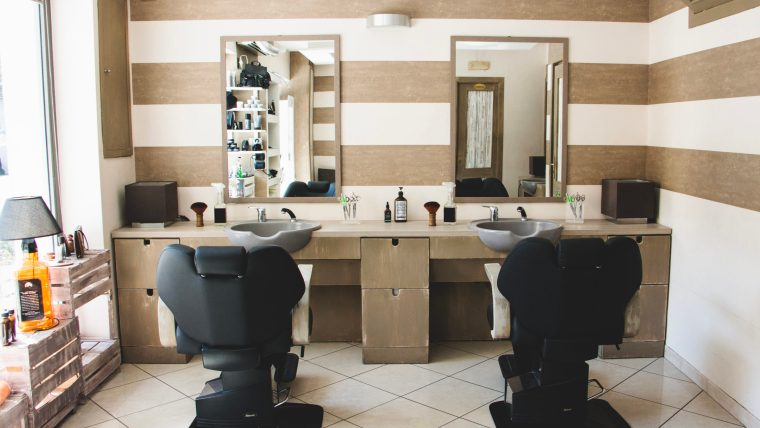 Two stations in a salon with hairdressing chairs and mirrors