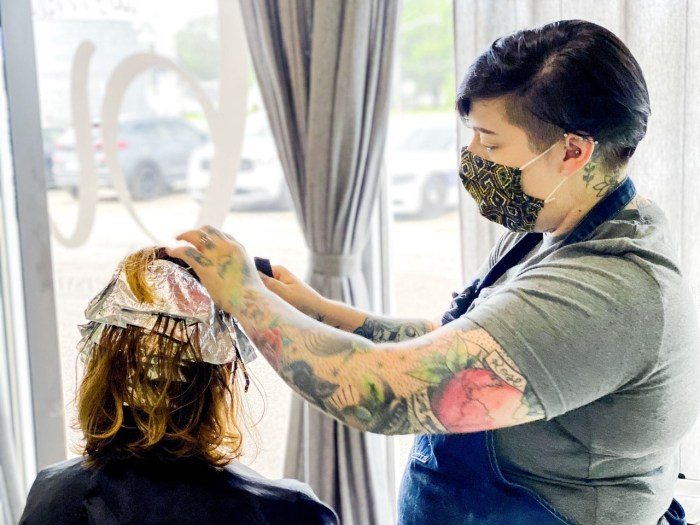woman wearing a mask working with customer to dye their hair