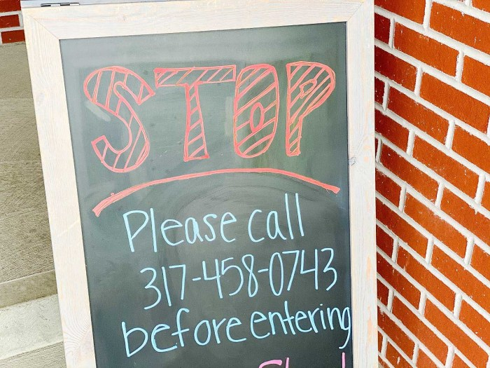 sign that says stop please call business before entering