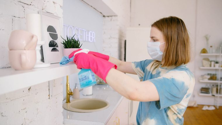 woman wearing a mask and gloves sanitizing a surface