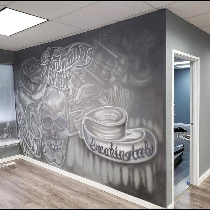 mural inside tattoo shop that says breaking ink