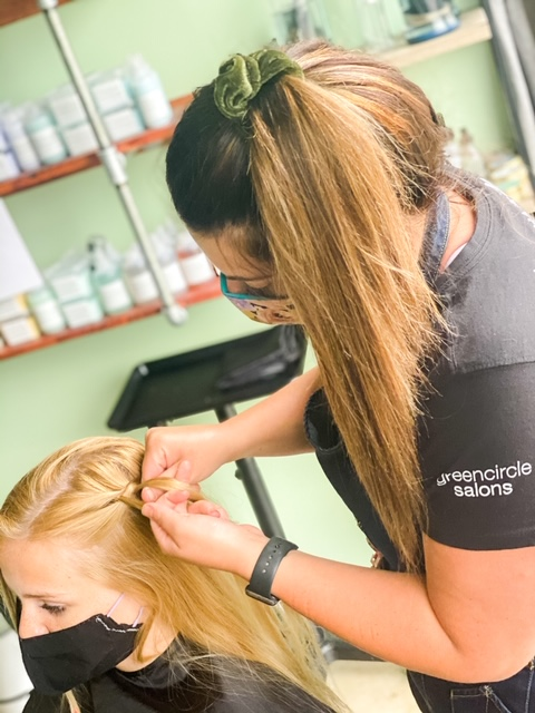 a woman wearing a mask braiding customers hair
