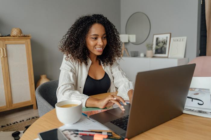 a woman smiling at her laptop