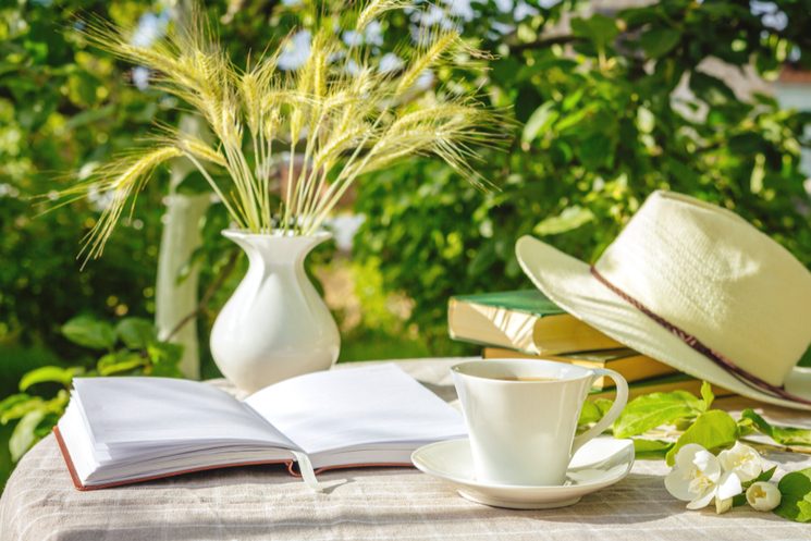 hat and books on garden table
