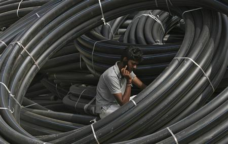 A construction supervisor speaks on a mobile phone amid rolls of underground telephone cable pipes on the outskirts of Hyderabad