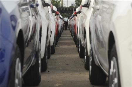 Employee walks between parked Hyundai cars ready for shipment at a port in the southern Indian city of Chennai