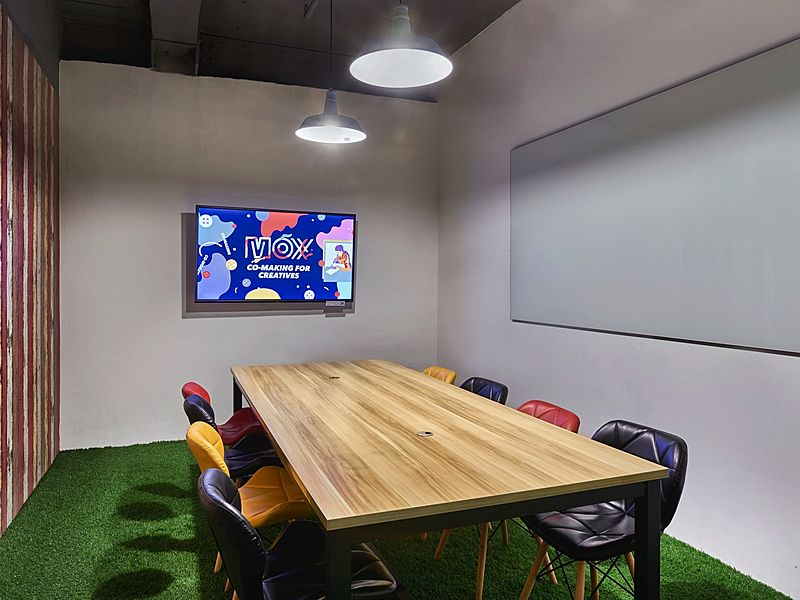 small discussion room in singapore with green floors and tv screen