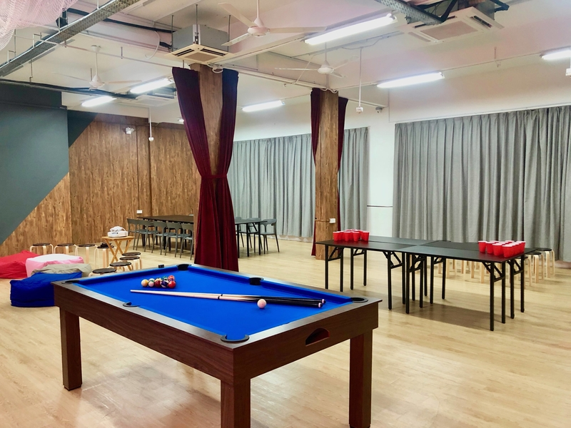 large multifunction room in singapore with pool table and grey drape
