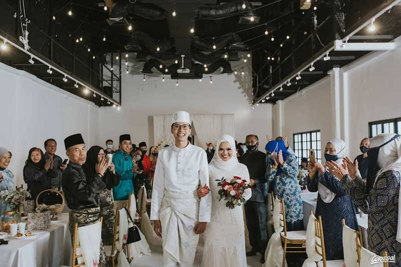 Malay couple walking down the aisle and family and friends clapping from sides