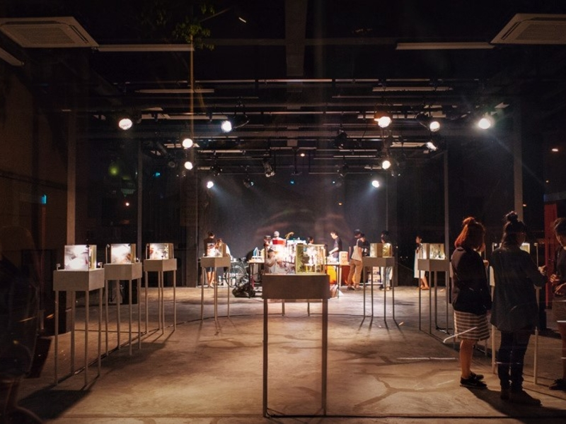 Dark exhibition space with stage lighting and people looking at art