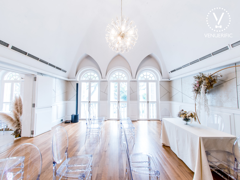 White venue with wooden floor, ceiling to floor windows and chandelier