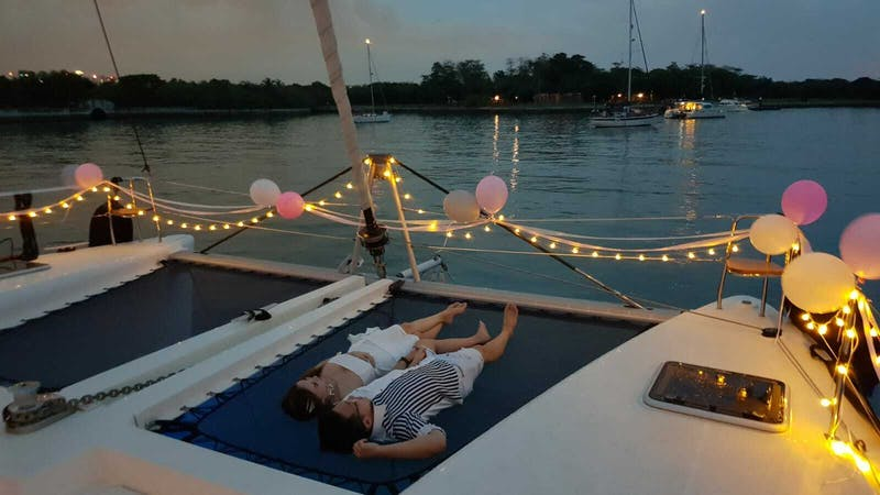 beautiful boat with fairy lights and couple laying on the deck for solemnisation