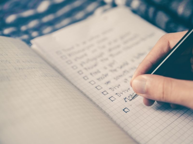 penning down to-do list in notebook