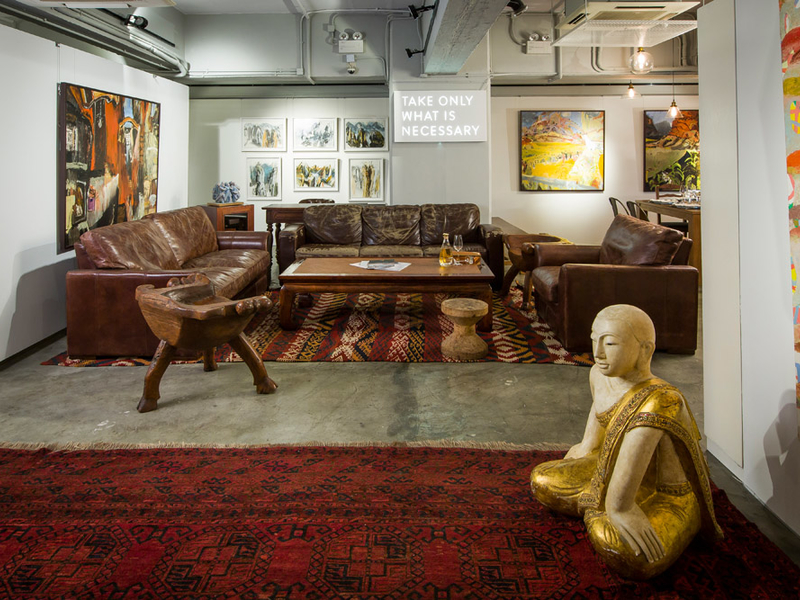 lounge area in a restaurant with sofa and paintings