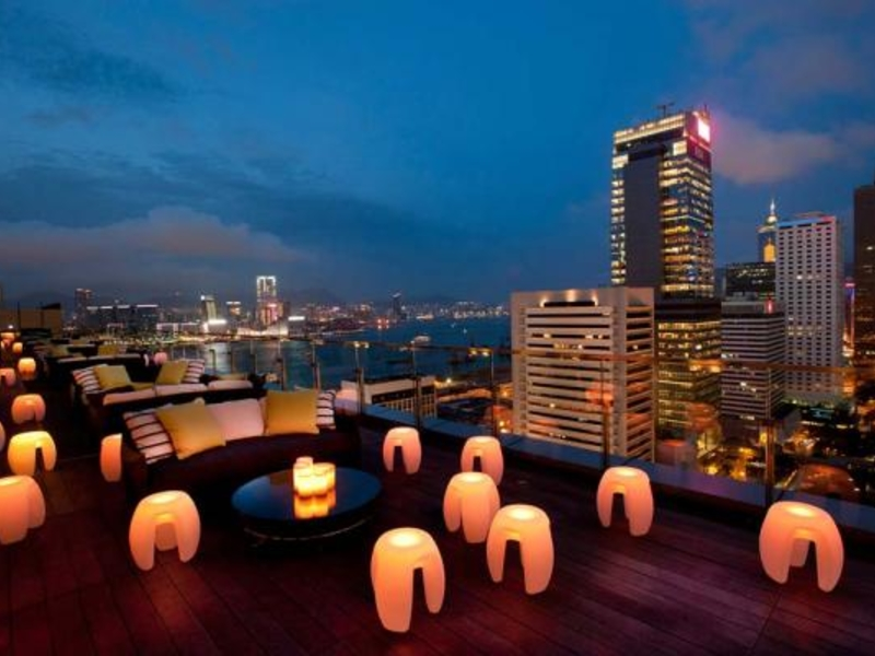 romantic rooftop seating area with lamps and view of the city
