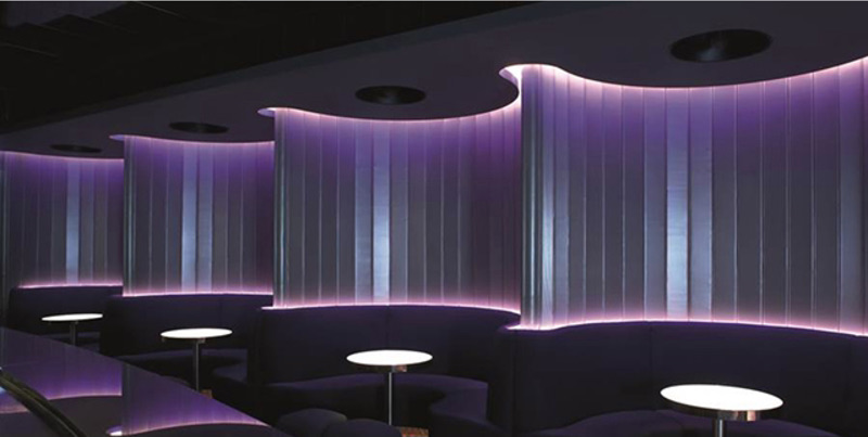 Sleek LED wall with round booth tables