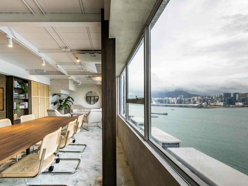 Room with long table, couches and a partial view of Hong Kong Harbour