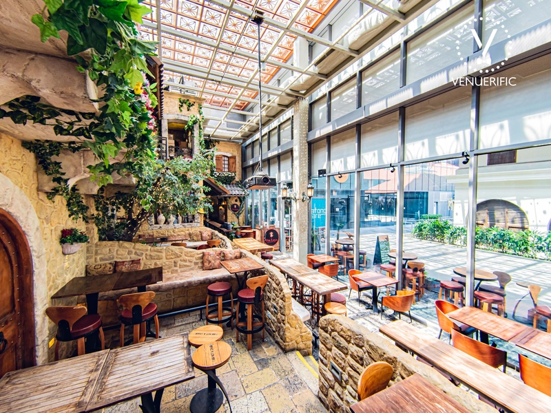 european inspired restaurant with plants and wooden furnishing