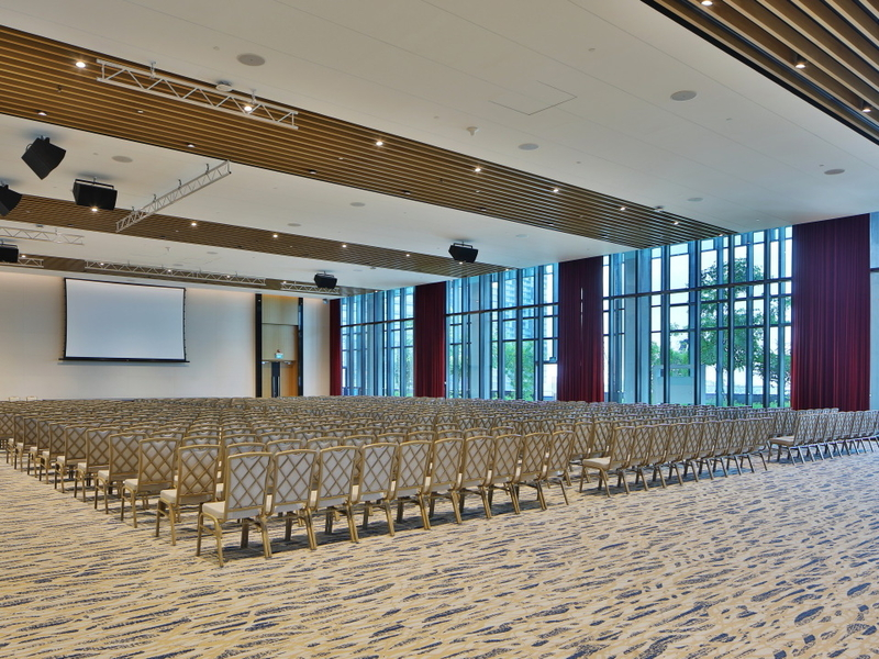 Large hall with many rows of seating facing a projector screen, and large floor to ceiling windows