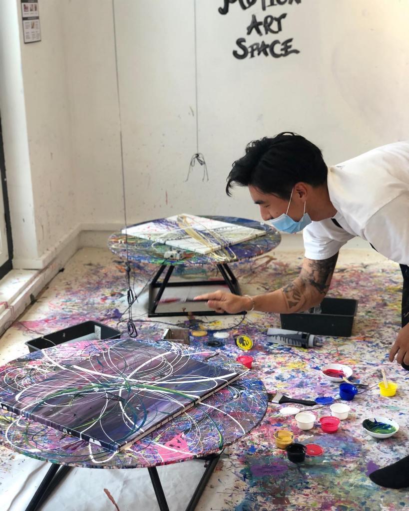 person splattering paint on canvas