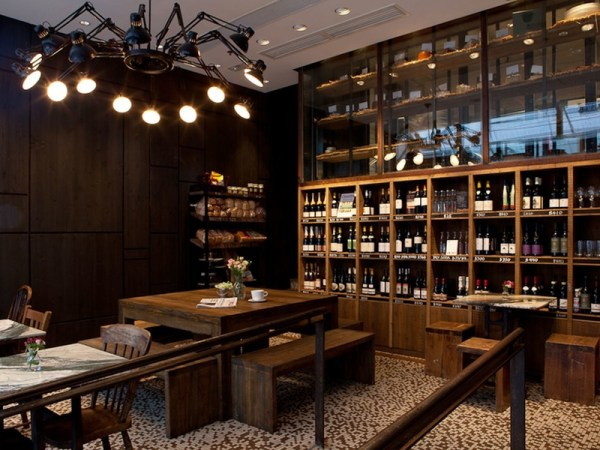 a dining area in a cafe with wine cabinet and chandelier
