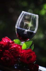 Glass of cold red wine, bouquet of red roses, on a caf terrace