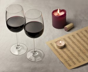 Two glasses of red wine, candles, and sheet music