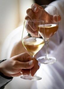 brindisi con calici di vino bianco