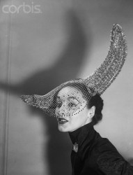 Original caption:1/11/52: High drama is achieved by Walter Florell in this rough grey straw with a soaring, cutaway brim. The white mesh veil is studded with red sequins.