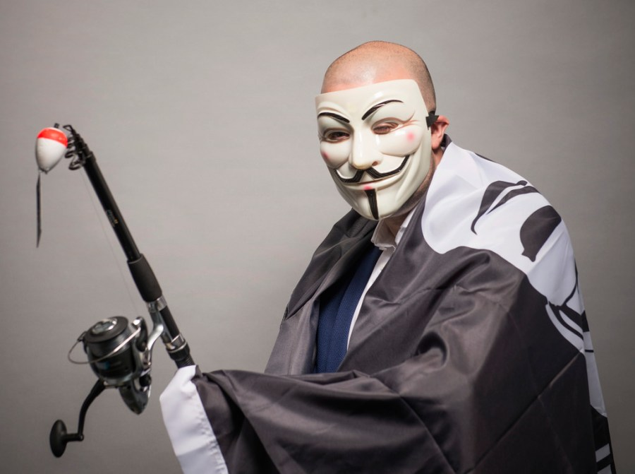 Phishing, persona utilizando máscara de Guy Fawkes (máscara Anonymous, V for Vendetta) cubierta por una bandera del mismo personaje y portando una caña de pescar