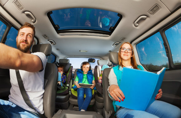 family on a road trip and busy children playing gadgets