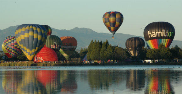Balloons rising over water