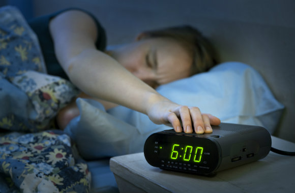 woman snoozing her alam clock