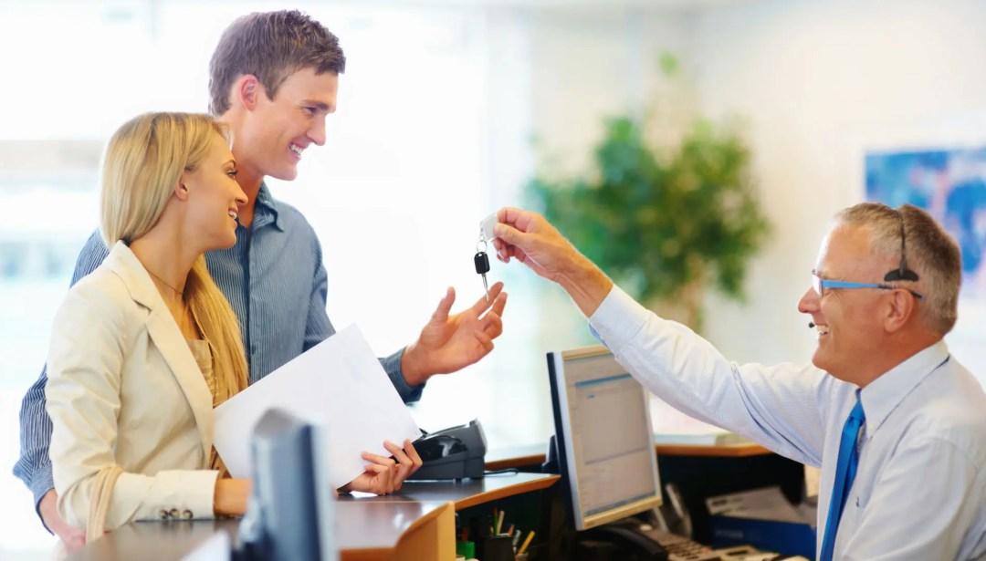 Rental car agent hands the keys to customers who know whether to purchase rental car insurance