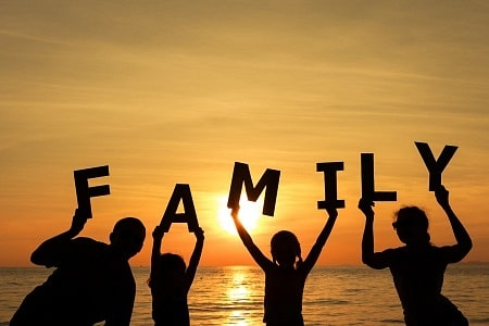 """Happy family standing on the beach at the sunset time. They keep the letters forming the word """" family"""". Concept of friendly family."""